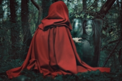 Mysterious red hooded woman in front of a magical mirror. Dark fantasy