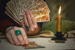 Tarot cards and fortune teller desk table. Future reading. Woman fortune teller holding in one hand a deck of tarot cards and shows a one card by another hand.