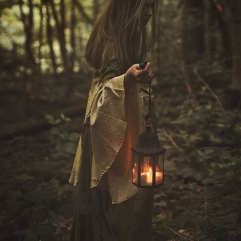 Fairy woman walking in a forest with lantern. Dark fantasy