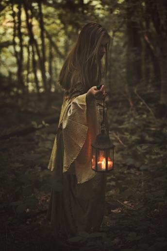 Fairy woman walking in a forest with lantern. Dark fantasy