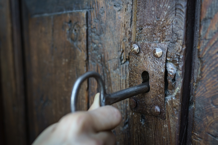 Selective focus vintage keyhole with key on a antique wooden doo