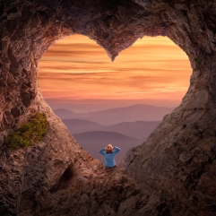 Young woman enjoying in idyllic mountain nature, celebrating freedom and sitting towards the beautiful sunrise. Valentines day concept.