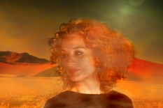 Morning fog in the desert. In foreground the portrait of a red haired woman with wonderful curls