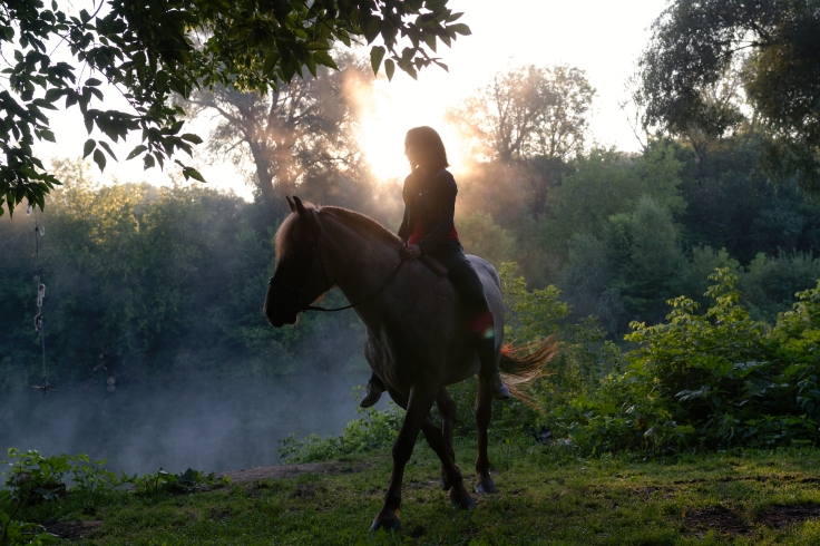 Young woman riding a horse on a beautiful landscape. Clear lake at morning fog. Sunrise
