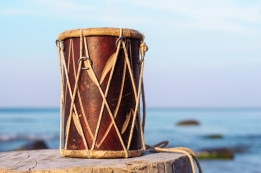 Wooden drum on the stump at the sea