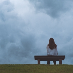 A woman sitting alone on a wooden bench in the park with cloudy and gloomy sky background