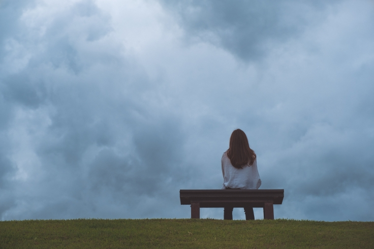 A woman sitting alone on a wooden bench in the park with cloudy