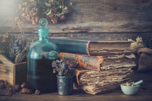 Tincture bottles, assortment of dry healthy herbs, old books, mo