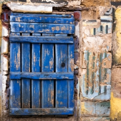 Old blue door against a yellow wall