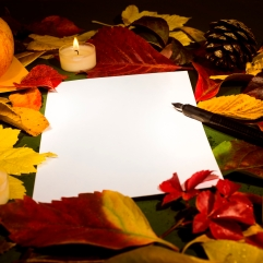 Autumn leaves, piece of paper, letter-cover, apple and candles, close-up photo. Copy space.