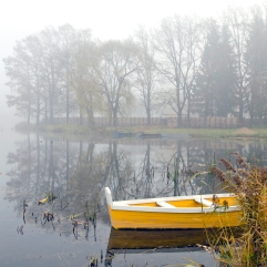 yellow wooden boat on autumn lake and early morning mist