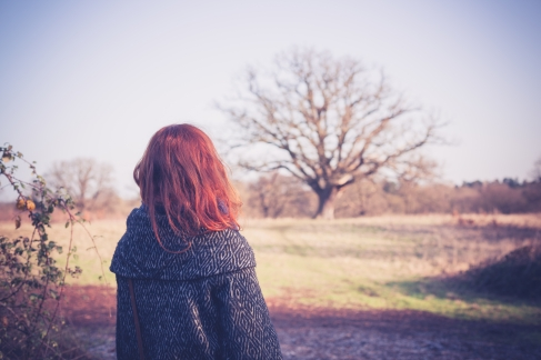 A young woman with red hair is walking in the countryside on a winter day
