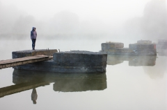 Autumn landscape with river. Ruined old bridge in morning mist. Girl at wooden pier is reflected in water
