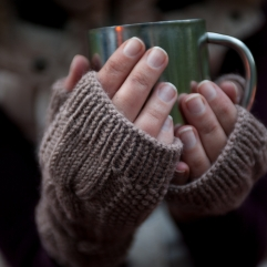 Metal mug with hot tea in a hands in a warm cozy mittens.