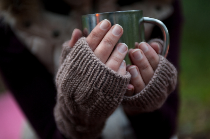 Metal mug with hot tea in a hands in a warm cozy mittens