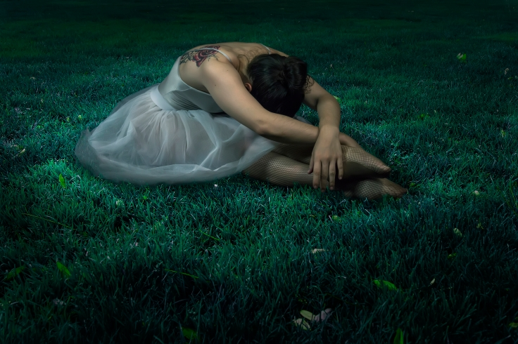 Dancer woman sitting on night grass scene