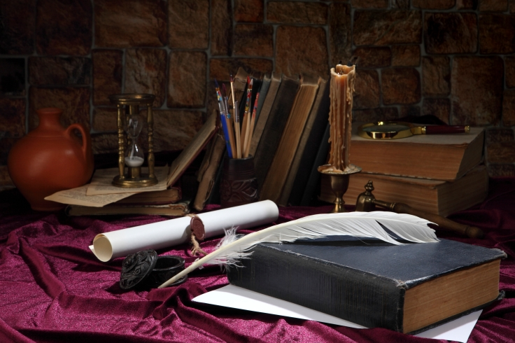 A goose feather, an inkwell, a scroll with a seal, a forged bronze candlestick with a candle, books, a magnifying glass and an hourglass on the desktop. Retro stylized photo. Selective focus.