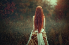 A beautiful young woman with very long red hair as a witch walks through the autumn forest. Back view. Creative colors and Artistic processing.