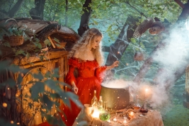 pretty young lady with blond curly hair above big magic cauldron with smoke and bottles with liquids, forest nymph in long bright red dress with loose sleeves prepares potion near wooden house.