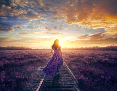 A woman in a colorful purple dress walks to a beautiful sunset.