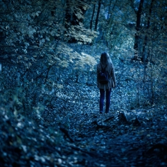 Woman walking alone on path in mystic dark forest. Lonely adult girl in strange creepy park at night in autumn. Young woman in fantasy spooky woods in twilight. Fear in scary mystery forest.