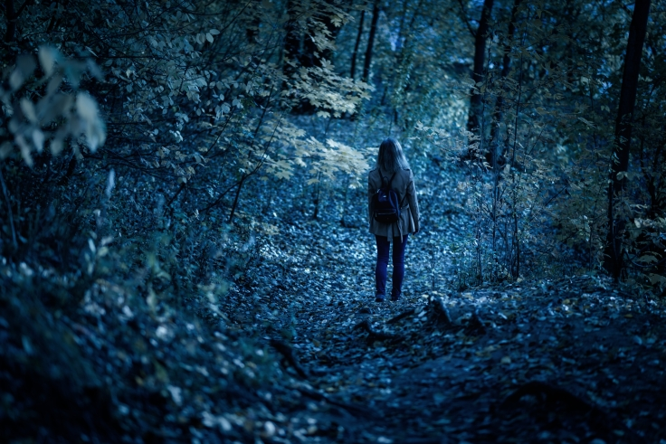 Woman walking alone on path in mystic dark forest. Lonely adult