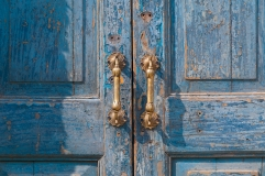 Architectural detail of a vintage brass door handle ,vintage antique door handle on the old blue wooden door