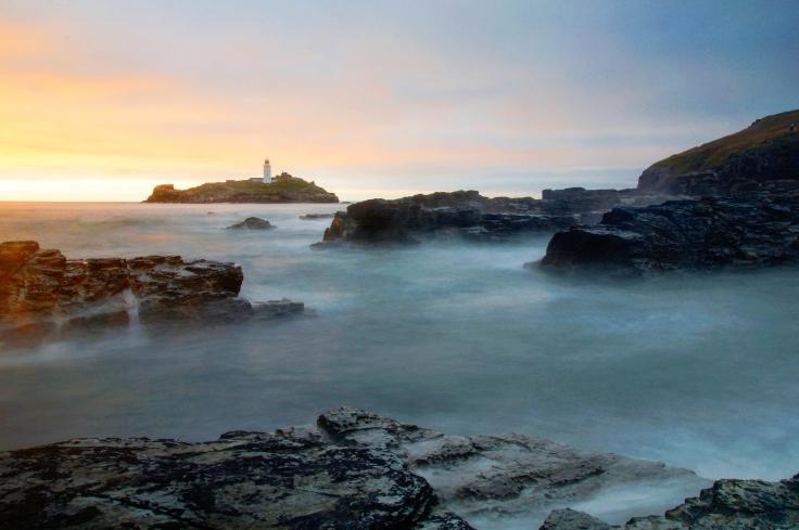 Misty lighthouse at sunrise sunset